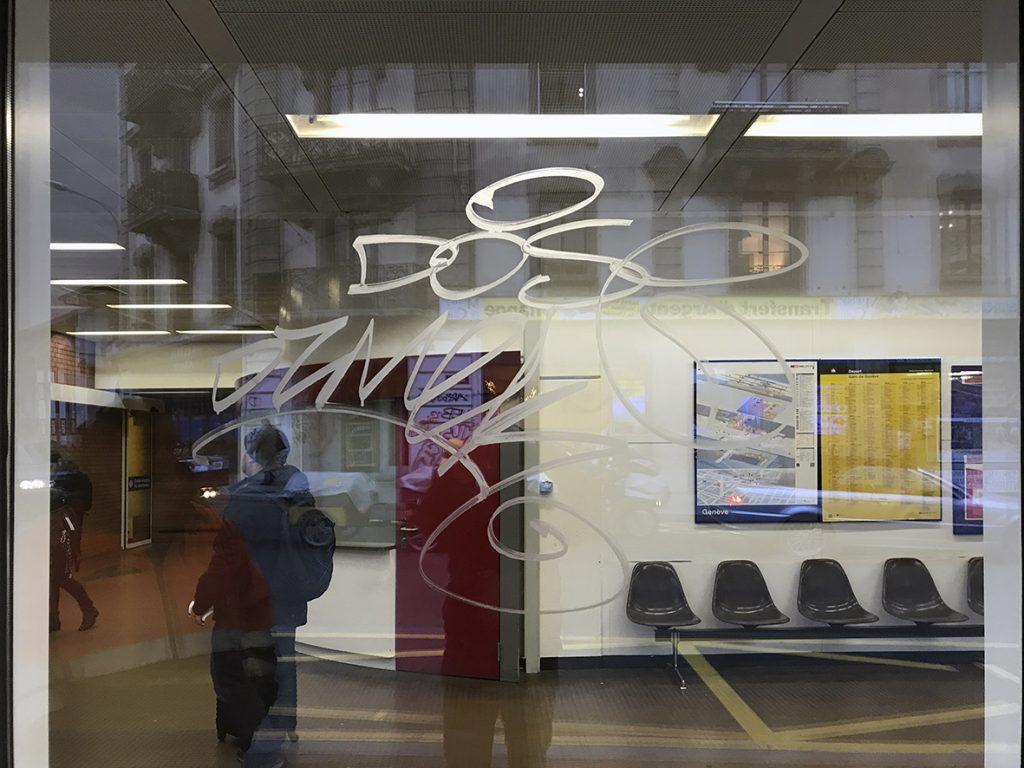 vitrine dégradée par un graffiti à la peinture
